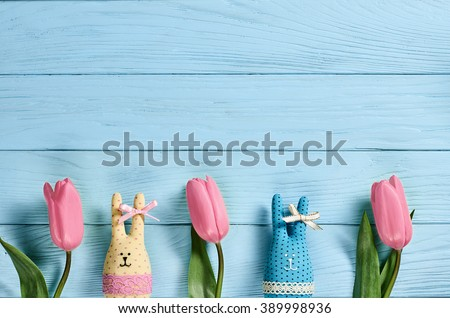 Easter background, rabbits and pink tulips. Happy bunny handmade and spring flowers on blue wood, copy space. Still life, top view. Unusual creative greeting card  - stock photo