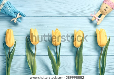 Easter background, rabbits and yellow tulips. Happy bunny handmade and spring flowers on blue wood, copy space. Still life, top view. Unusual creative greeting card  - stock photo