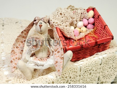 easter background with a handmade linen rabbit with long floral pink ears and bright basket with beige and pastel pink candy eggs in vintage provence style - stock photo
