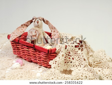 easter background with a handmade linen rabbit with long floral pink ears seating inside a bright basket with beige and pastel pink candy eggs on hand knitted lace tablecloth - stock photo