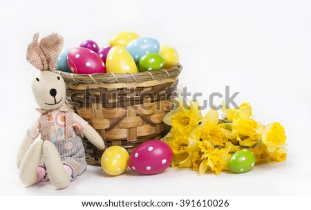 Easter background with colorful Easter eggs and a bouquet of yellow daffodils and cute bunny