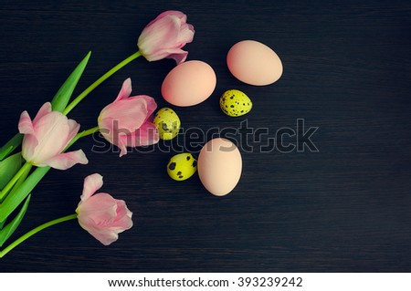 Easter background with colorful eggs and pink tulips over dark wooden background. Happy Easter. Easter Holiday flowers bunch with bright eggs. Spring flowers. Top view with copy space. - stock photo