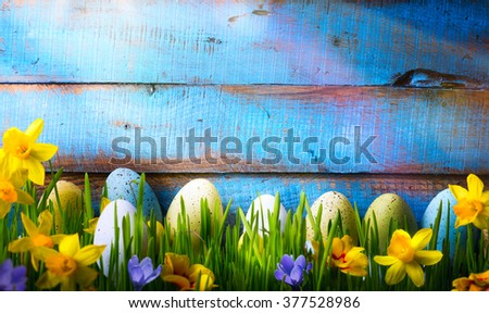 Easter Background with easter eggs and spring flowers on green grass - stock photo