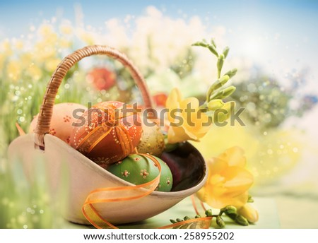 Easter background with eggs and spring flowers, shallow DOF, focus on the part of front egg with the ribbon. This image is toned. - stock photo