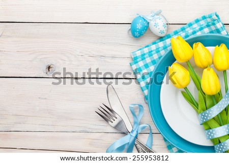 Easter background with yellow tulips and colorful eggs over white wooden table. Top view with copy space - stock photo