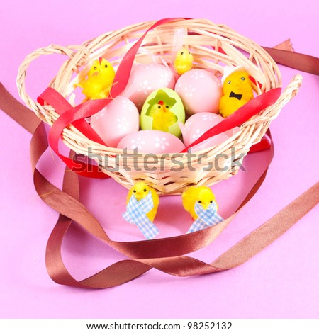 Easter basket filled with eggs and with chicken on a pink background - stock photo