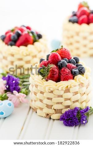 Easter basket mini cakes with glazed fresh fruit on top. - stock photo
