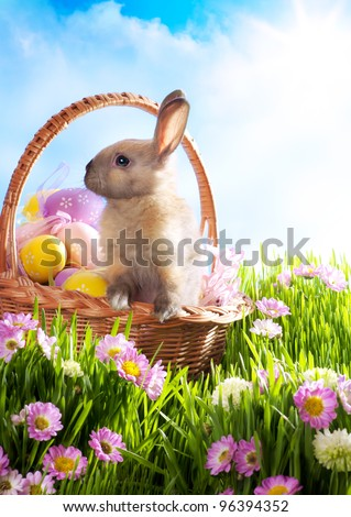 Easter basket with decorated eggs and the Easter bunny in the grass - stock photo