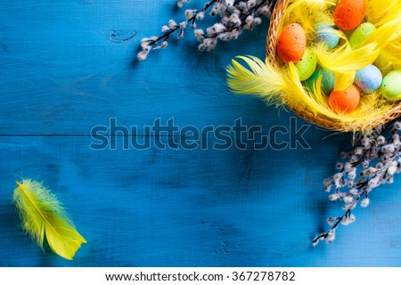 Easter Basket with easter eggs and yellow feathers and catkins on blue wooden background. - stock photo