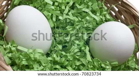 Easter Basket with Grass and Two White Eggs Close Up. - stock photo