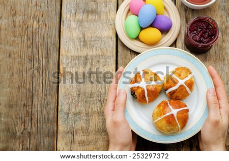 Easter Breakfast. Man holding the plate with the buns with a cross. tinting. selective focus - stock photo