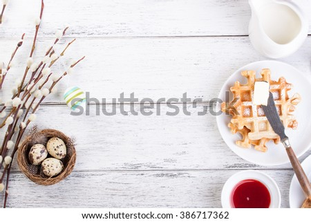 Easter breakfast with quail eggs, waffles, fruit jam, milk and sandwiches, with willow branch on a white wooden background, top view with copy space - stock photo
