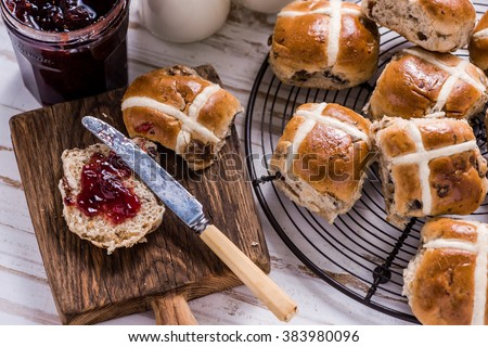 Easter breakfast with traditional hot cross bun and jam. From above on wooden table. - stock photo