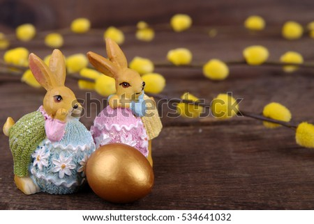 Easter bunnies, golden egg with bow and branches of pussy-willow on a dark wooden background.