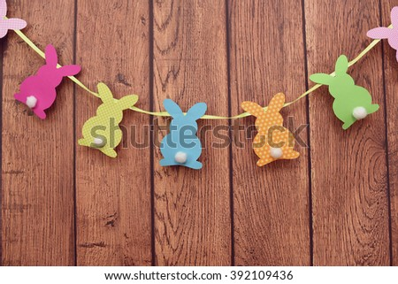 Easter bunnies hanging on a wooden background