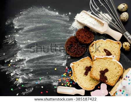 Easter bunny cake preparing in kitchen. Holiday food background with creative cake and baking ingredients on black background top view with copyspace - stock photo
