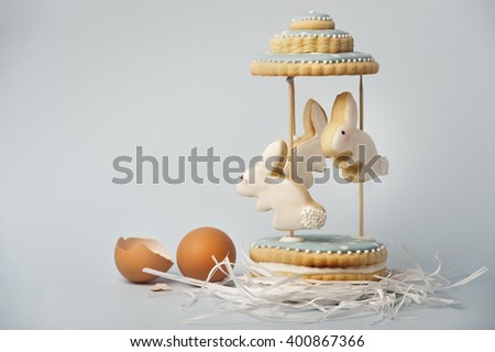 Easter bunny cakes on a roundabout on a blue background - stock photo