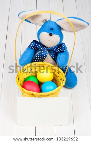 Easter bunny, eggs in basket, greeting card on white wood background - stock photo