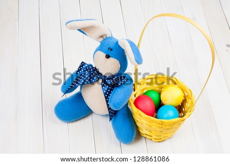 Easter bunny, eggs in basket on white wood background - stock photo