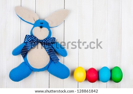 Easter bunny, eggs on white wood background - stock photo