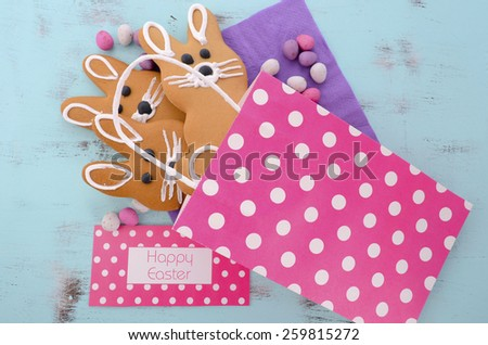 Easter bunny gingerbread cookies in pink polka dot gift bag on blue wood table.  - stock photo