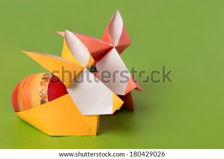 Easter bunny paper rabbit with painted egg on a grass green background - stock photo