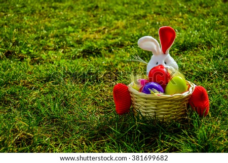 Easter bunny watching the egg hunt - stock photo