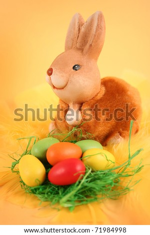 easter bunny with colored eggs on yellow background