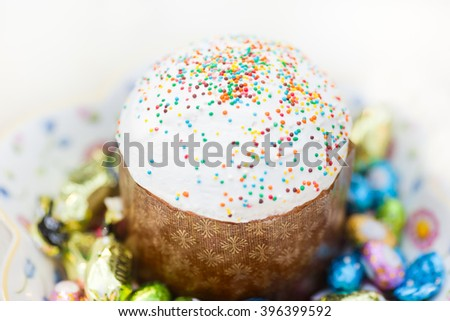 Easter cake and Easter eggs and candies over white background. Selective shallow focus - stock photo