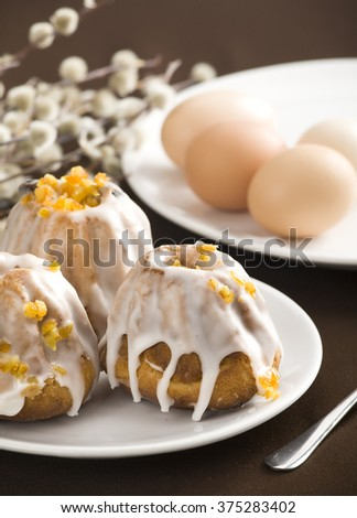 Easter cake on white plate. All on brown table cloth. - stock photo