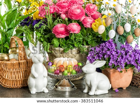 Easter cake, spring flowers, eggs and bunnies. Festive home interior decoration - stock photo