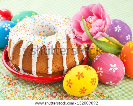easter cake, tulip and colorful eggs on kitchen table - stock photo