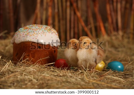Easter cake with colored eggs and chickens in the hay.