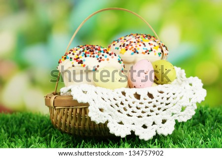 Easter cake with eggs in wicker basket on grass