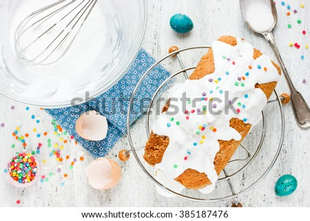 Easter cake with white icing and colorful sprinkling on a white table. Preparation cute Easter cake with chocolate bunny inside - stock photo