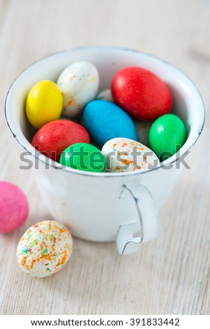 Easter candy eggs on white wooden surfae