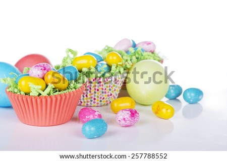 Easter Candy in colorful cupcake wrappers with green grass confetti and dyed Easter eggs - stock photo