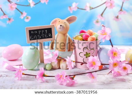 easter card with funny  clay rabbit ,eggs and chalkboard with greetings text on blue sky background - stock photo