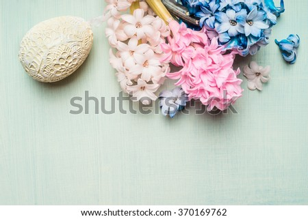 Easter card with  hyacinths flowers and decor egg on light green background, top view.  - stock photo