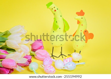 Easter chickens, pink tulips and eggs over yellow paper - stock photo