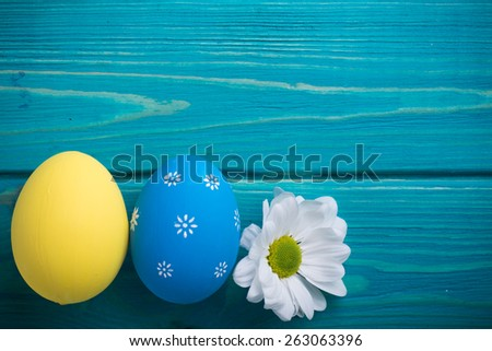 easter colored eggs with lace ribbon and flower on blue wooden background Ukrainian national flag colors