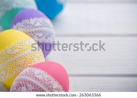 easter colored eggs with lace ribbon on white wooden background