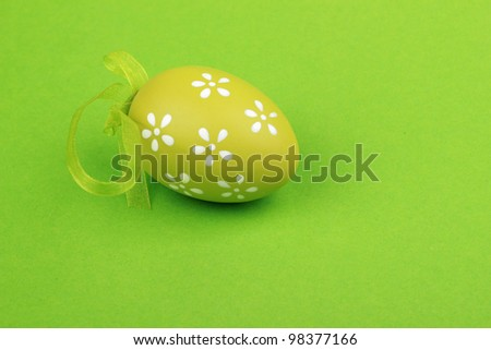 Easter composition for holiday postcard as a green with small lovely white flowers painted egg on green background/green painted egg - stock photo