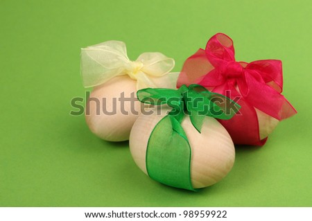 Easter composition for holiday postcard as a three wooden colorful eggs on green background/Three easter eggs - stock photo