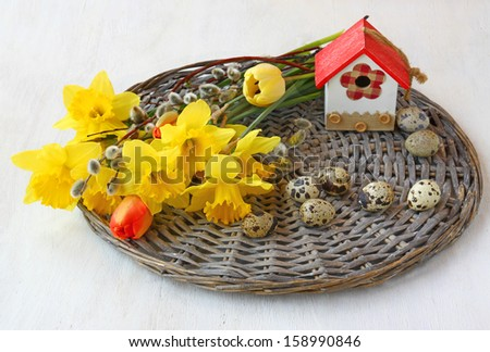 Easter composition of a bouquet of daffodils and tulips, twigs of willow, quail eggs and decorative birdhouse on a wicker round - stock photo