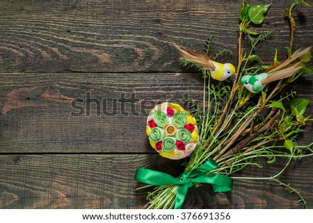 Easter composition of green branches with green ribbon, egg in quilling techniques and decorative birds on the old wooden background with copy space for text - stock photo