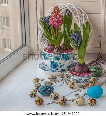 Easter composition on the windowsill of hyacinths, eggs and willow branches - stock photo