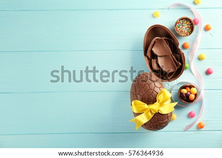 Easter composition with chocolate eggs on color wooden background, space for text