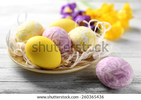 Easter composition with colorful eggs on plate on wooden table background - stock photo