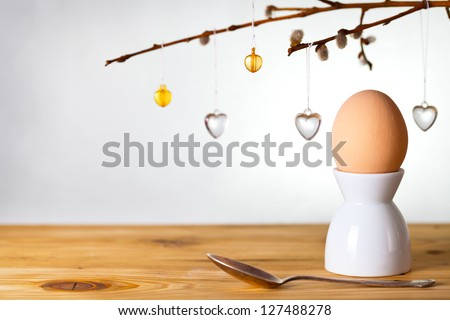 Easter composition with egg and catkins on wooden background. Egg painted a beige paint